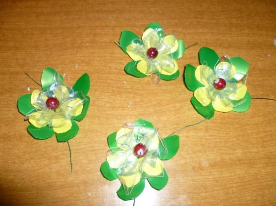 Из бросового материала мы в детском саду сделали цветы.  Картину из цветов разместили на пластмассе.