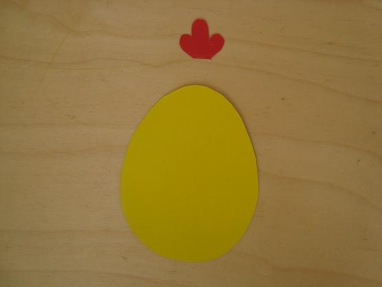Из красного картона вырезаем два гребешка для цыплят и приклеиваем к одному из овалов с цветной стороны.