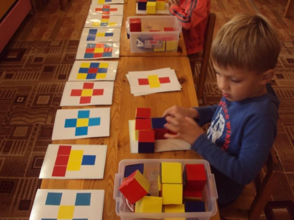 строит из кубиков модель,