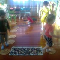 Фотоотчет о проведении подвижной игры с детьми младшего возраста «С кочки на кочку»